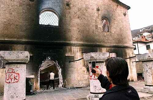 Etničtí Albánci ničili všechny křesťanské svatyně v Prizreni, a při tom 3800 německých vojáků stálo, dívalo se a dělalo si fotografie. Tato AP fotografie ukazuje kosovského Albánce močícího ve vchodu do prizrenské katedrály sv. Jiří. Biskup Artemij dostal písemnou záruku, že němečtí vojáci budou tuto katedrálu ochraňovat.