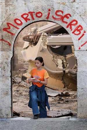 Kosovští Albánci: Smrt Srbům! Albánská dívka si něco odnáší z trosek prizrenské pravoslavné katedrály sv. Jiří právě zničené kosovskými Albánci